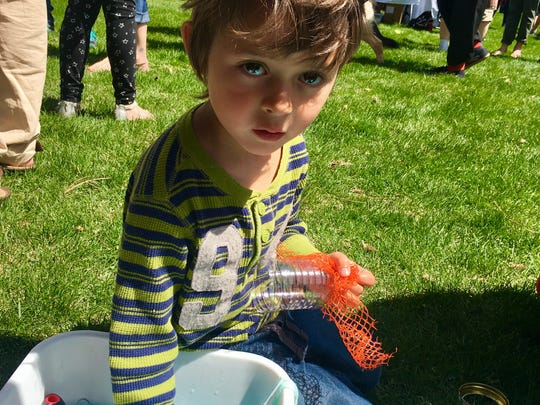 4-year-old Jonathan Van Fosson mixes bubble juice at the Reno celebration of Earth Day on April 22, 2018.