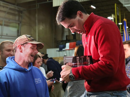 Wisconsin Gov. Scott Walker signs his book for Joe Spiering, left,  of Green Bay at a campaign rally at K.I. Inc in Green Bay Wis., on Monday, Nov. 3, 2014.