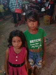 Two girls pose for the camera at a market in Cambodia