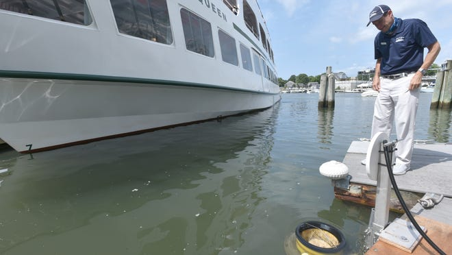 Island Queen General Manager Todd Bidwell checks on the Seabin floating just off the bow of the ship attached to the dock in Falmouth Harbor. The device from Australia vacuums up microplastics and small debris from the water.