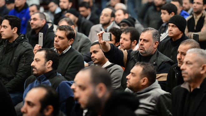 Men in the crowd record on their cellphones as U.S. Sen. Bob Menendez visits the Islamic Center of Passaic County after Friday afternoon prayers to speak out against President Trump's ban on travelers from seven predominantly Muslim countries.
