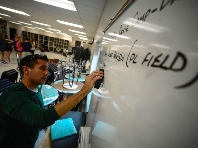 Greg Harris, the band director at Vestal High School, writes down the schedule for the second day of rookie band camp held at Vestal High School on Wednesday.