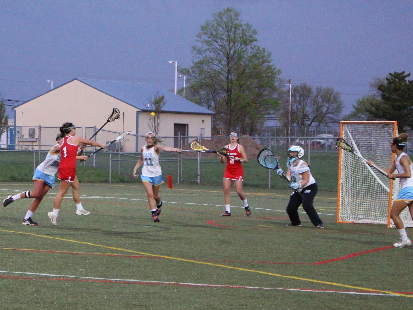 Worcester Prep's Sophie Brennan (1) shoots and scores past Cape Henlopen goalkeeper Sam Broadhurst for one of her five goals. Prep came back to win 14-13 in double overtime at Cape on Wednesday.