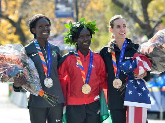 Second-place finisher Sally Kipyego (left) and first-place finisher Mary Keitany (middle) and third-place finisher Molly Huddle (right) pose for a photo during the 2016 TCS New York City Marathon.