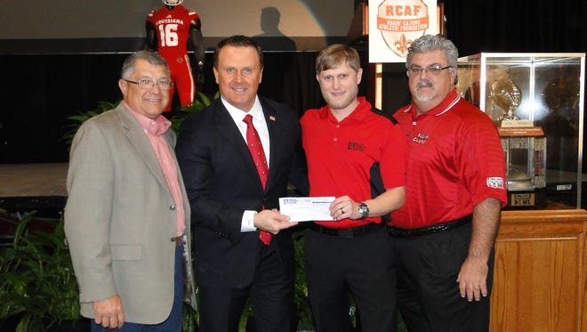 Gulf Coast Bank presents  a donation check to Coach Mark Hudspeth. Murphy Guilbeaux, Gulf Coast Bank business development officer; Mark Hudspeth, UL head football coach; Jason Patout, GCB vice president; and Greg Harrington, GCB vice president.