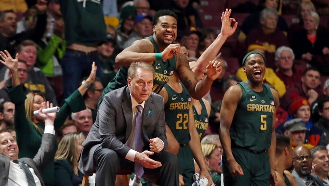 Michigan State players celebrate behind coach Tom Izzo late in the second half of an 87-57 win over Minnesota on Tuesday, Feb. 13, 2018 in Minneapolis.