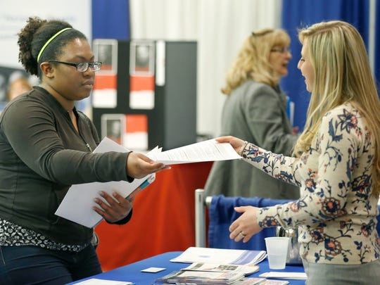 Pa' Seana Nelson of Gates hands paperwork to Dana Voldan, with Bryant & Stratton College during the Career Expo 2015 at the DoubleTree by Hilton Hotel Rochester.