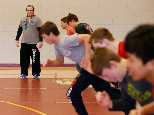 Coach Justin Kuhn runs wrestlers through drills as