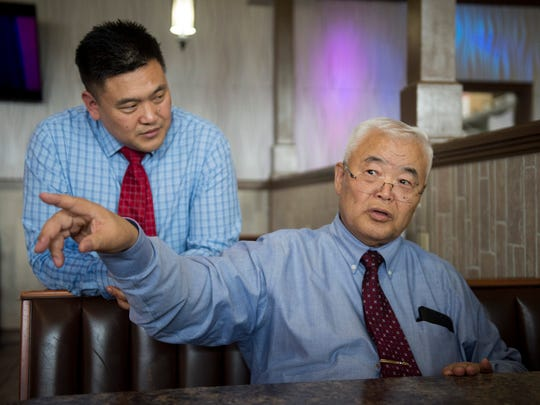 Owner Joe Kim, left, listens to his father, Suk Ki tell stories of his life in Korea at Gangnam restaurant in Owensboro, Ky. on Wednesday, May 30, 2018. Joe is planning an event to showcase his father's story and Korean cuisine.