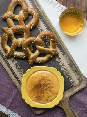 Soft pretzels are served with hot Cheddar cheese beer dip.