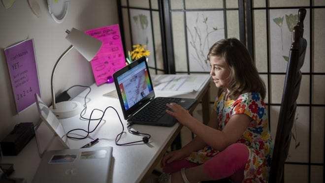 Third grader Lydia Parker, who is medically compromised, uses her Google Chromebook laptop in her Pickerington home. The 9-year-old is enrolled in the Pickerington school district's online academy and takes all her classes at home.