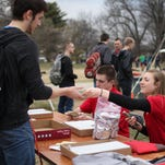 Sophomore Zach Vierkandt and freshman Megan Elliott hand out meal buttons Monday during Veishea's Campus Cookout. The $5 buttons allow students access to the week's meal offerings on Central Campus.