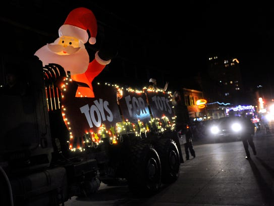 An inflatable Santa Claus waves from the back of a U.S. Marine Corps truck during Tuesday's City Sidewalks Lighted Christmas Parade.