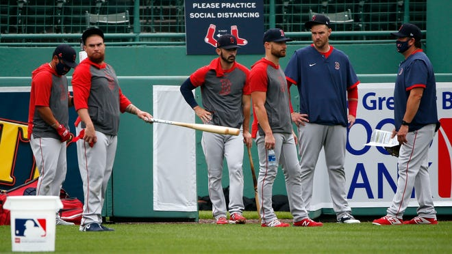 Red Sox players stand on the field during Summer Camp practice at Fenway Park.
