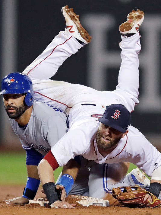 Boston Red Sox second baseman Dustin Pedroia lands on Toronto Blue Jays' Jose Bautista after turning a double play during the 11th inning of a baseball game at Fenway Park in Boston, Tuesday, July 18, 2017. Russell Martin was out at first. (AP Photo/Charles Krupa)