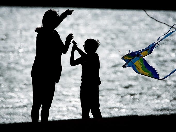 Amber Cole helps her son Taylor Cole, 9, get his kite