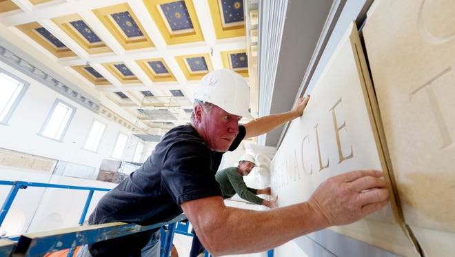Tim Williams carefully places a piece of ornamental frieze to the wall at the Sacred Heart Cathedral construction site on Northshore Drive in Knoxville on Oct. 19, 2017.