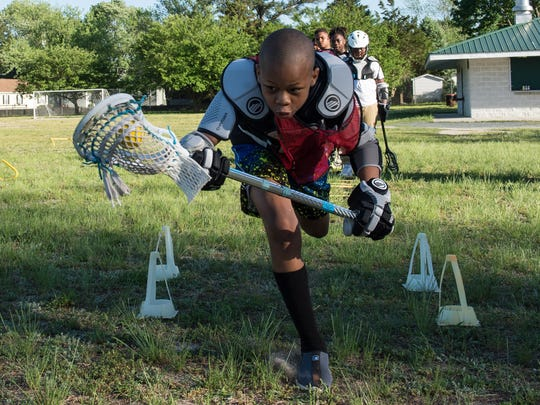 Lensky Saintil, 12, practices a lacrosse drill at Doverdale Park.