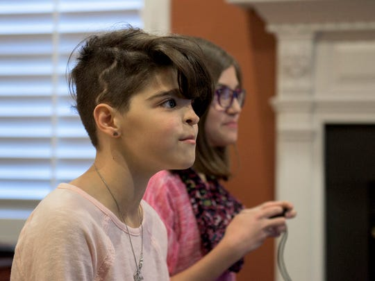 "Maryelena Baldassarre, 11, left, plays video games with her twin sister, Annalisa Baldassarre, at their Sicklerville home. Maryelena opted to show off the lightening bolt-shaped scar on her scalp with a short new haircut. ""It's cool,"" she says."