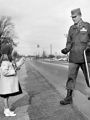 Francile Yates, 5, stopped Sgt. James F. Wiggins about three miles north of Frayser on Jan. 30, 1956, to contribute her gift to a total of $77.47 collected for the day for the March of Dimes. The hiking Memphis recruiter has collected $1,828.11 since he marched out of Union City, Tennessee, the previous week. Francile is the daughter of Mr. and Mrs. Cullen Yates of 5349 Hwy 51 North.