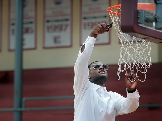 Alex Lomax cuts a piece of net in the East High School gymnasium for himself as members of Penny Hardaway's championship basketball team gather for a rally to recognize their national ranking by MaxPreps.