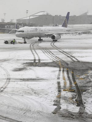 A United Airlines airplane leaves tracks in the snow  at Newark Liberty International Airport on Feb. 3, 2014.