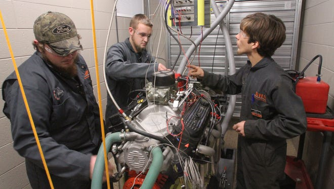 Automotive tech students Brandon Bonin, Travis Schmidt and Kyle Schneider check the intricate web of sensors, wires and pipes connecting a Chevrolet LT1 eight-cylinder engine to Brighton High School's new engine dynamometer. The $51,000 piece of equipment allows students to understand engine performance and diagnostics to a much higher degree than previously possible.