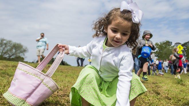 Mia Thibodeaux, 3, grabs an Easter egg.