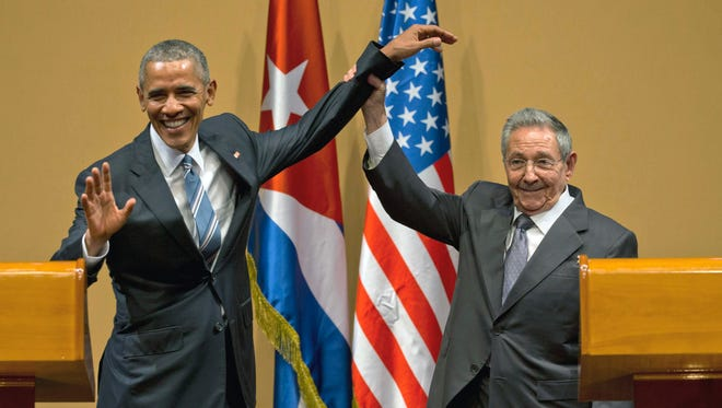 In this March 21, 2016 file photo, Cuban President Raul Castro, right, lifts up the arm of President Obama at the conclusion of their joint news conference at the Palace of the Revolution, in Havana, Cuba.