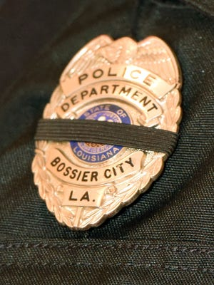 A black band wraps around the badge of a Bossier City Police Offer during a  prayer service for law enforcement at City of Truth Worship Center in Bossier City.