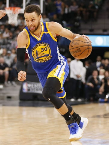 Stephen Curry dribbles the ball as Patty Mills defends