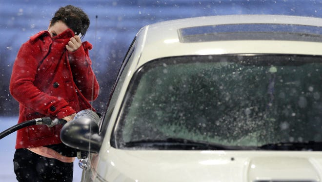 Taylor Bridge blocks her face from the wind while filling her car with gas as the first major snow storm of the winter blows through the Fox Valley on Monday, December 28, 2015, in Kimberly, Wis. Wm. Glasheen/Post-Crescent Media