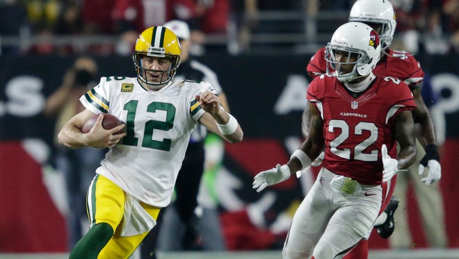 Green Bay Packers quarterback Aaron Rodgers runs for a first down in the first quarter against the Arizona Cardinals.