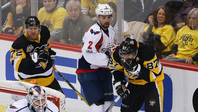 Pittsburgh Penguins' Sidney Crosby (87) reacts after being in a collision with Washington Capitals' Matt Niskanen (2) and Penguin' Patric Hornqvist (72) during the first period of Game 6 in an NHL Stanley Cup Eastern Conference semifinal hockey game in Pittsburgh, Monday, May 8, 2017. Crosby remained in the game.