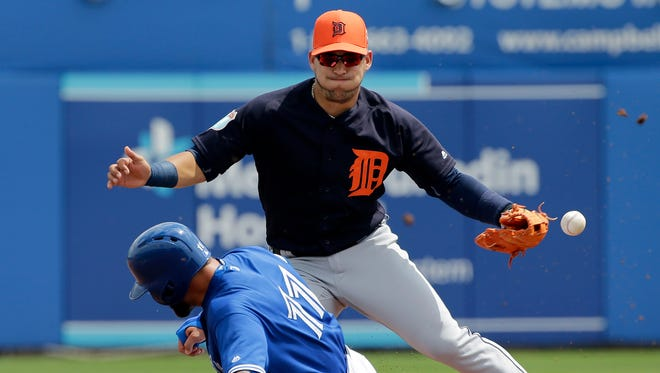 Toronto Blue Jays' Kevin Pillar steals second base as Detroit Tigers shortstop Jose Iglesias drops the ball during the first inning of a spring training baseball game Thursday, March 24, 2016, in Dunedin, Fla.