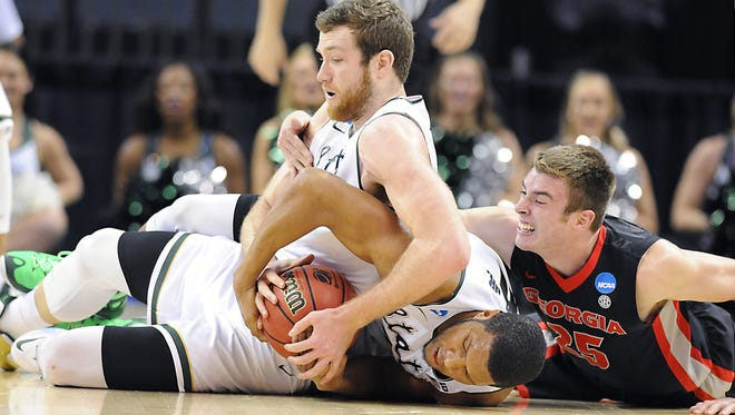 MSU's Matt Costello, left, and Marvin Clark Jr., center, tie up the ball  against Georgia's Kenny Paul Geno during the first half of their NCAA tournament game Friday in Charlotte.