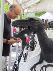 This dinosaur isn't really attacking a visitor to GlassFest in Corning on Sunday. It's part of a display by Roland Metal Art of Carrolltown, Pa.