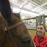 Izzi Bryson, 13, from Loveland, laughs at the braid she gave her horse, Slingshot, on the second day of 4-H Horse Show in the Ranch-Way Feeds Arena at the Larimer County Fair Monday, July 27, 2015.
