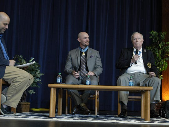 Staff Sgt. Ty Carter, center, and Lt. Col. Bruce Crandall, right, answer questions from Creek Wood High School students. Carter and Crandall are Medal of Honor recipients.