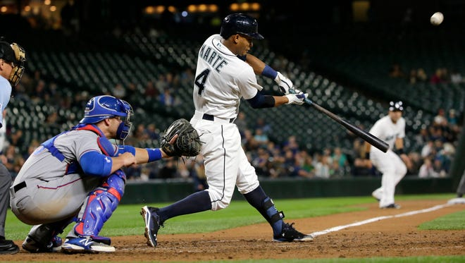Seattle Mariners' Ketel Marte grounds out in the seventh inning of a baseball game as Texas Rangers catcher Chris Gimenez watches, Tuesday, Sept. 8, 2015, in Seattle. Jesus Montero scored on the play.
