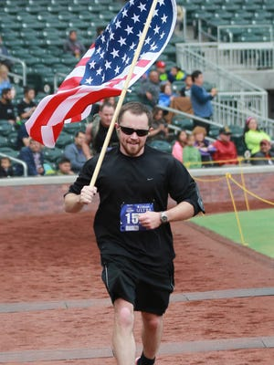 Ryan Elliott of Operation Flagpole ran holding Old Glory during the El Paso Marathon on Feb. 21 at Southwest University Park. More than 2,000 runners participated in the full marathon, the half-marathon and the 5K run/walk.