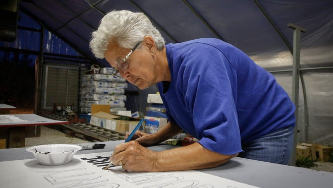 """Mary VanPelt paints a sign to support the """"Vote Yes"""" campaign to approve a ballot measure in November to build a single county courthouse in the middle of Lee County. Currently, Lee County is the only county in the state with two county seats, Fort Madison and Keokuk. Members of the committee to vote yes have been working to produce literature, media and a detailed YouTube video on the cost-savings analysis and other details regarding the courthouse."""