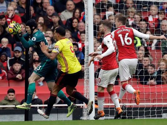 Arsenal goalkeeper Petr Cech, left, makes a save in front of Watford's Troy Deeney during the English Premier League soccer match between Arsenal and Watford at the Emirates stadium in London, Sunday, March 11, 2018. (AP Photo/Matt Dunham)