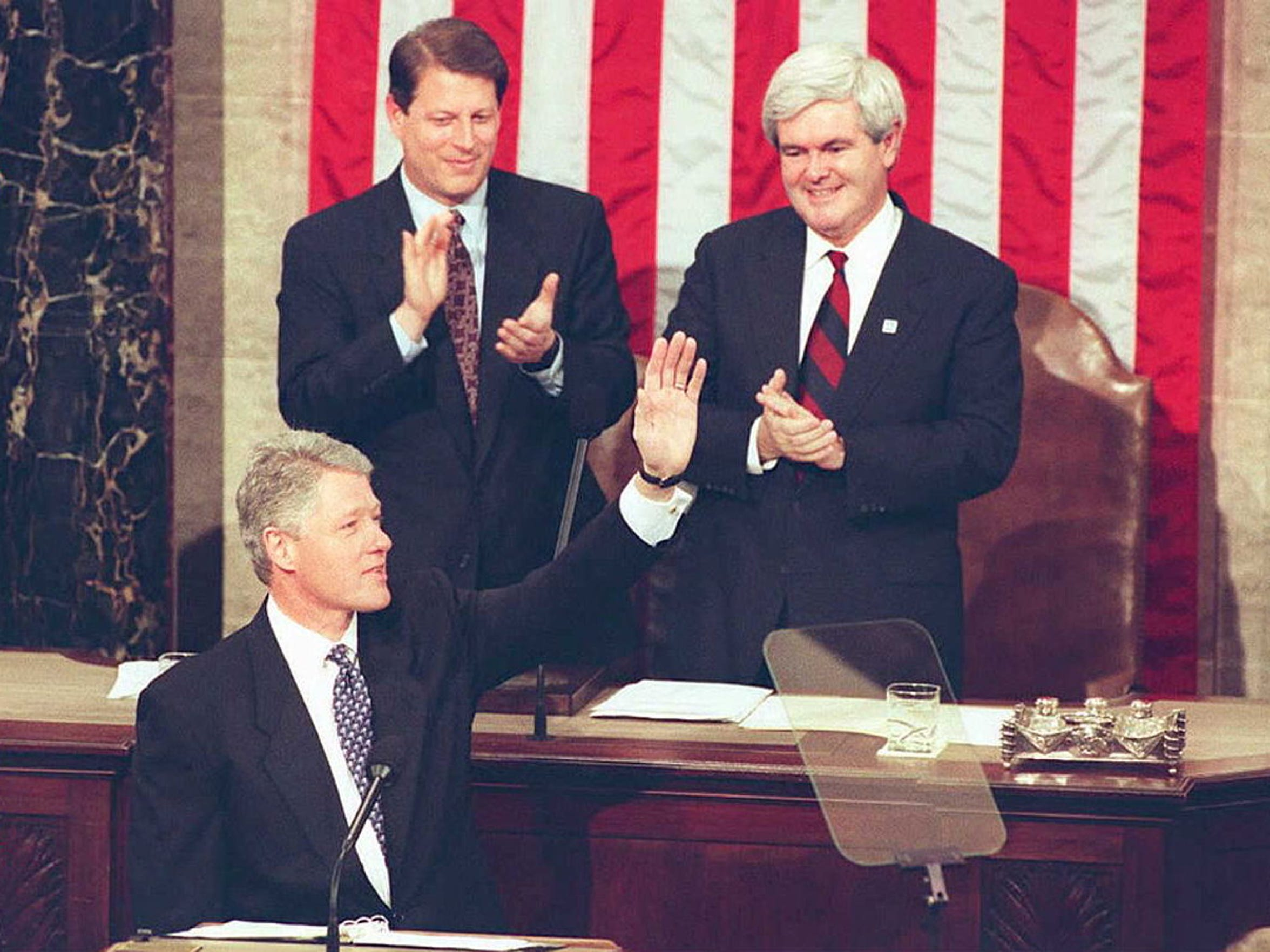 "WASHINGTON, DC - JANUARY 24:  US President Bill Clinton waves to members of Congress 24 January 1995 as Speaker of the House of Representatives Newt Gingrich (above,R) and Vice President Al Gore(above, L) applaud before the beginning his second State of the Union address. In his speech, President Clinton called for a new social compact,  ""to meet the challenges of our times.""   (COLOR KEY: Flag has red stripes.)  AFP PHOTO  (Photo credit should read LUKE FRAZZA/AFP/Getty Images)"