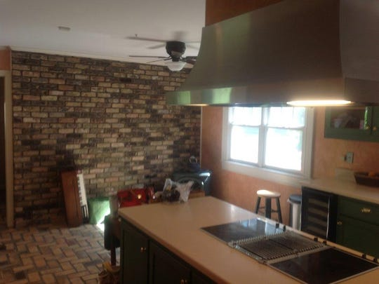 BEFORE of kitchen with brick flooring, detached vented hood and dated colors and materials.