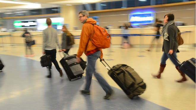 In this Tuesday, Dec. 23, 2014 photo, travelers leave the Jacksonville International Airport after claiming their luggage in Jacksonville, Fla.  Christmas Eve is shaping up to be windy, wet and warm instead of white across much of the country, creating headaches for some travelers, especially in the Great Lakes and the Northeast.