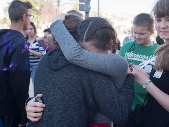 Unidentified young people embrace after being evacuated