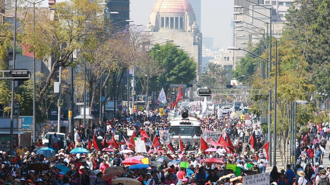 Thousands of people belonging to trade unions participate Friday in a rally in Mexico City to demand the government call for a referendum on the energy reform enacted in December. The reform was part of a deal to end a ban on re-election, signed into law Friday.