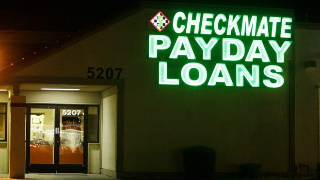 Neon signs illuminate a payday loan business in Phoenix.