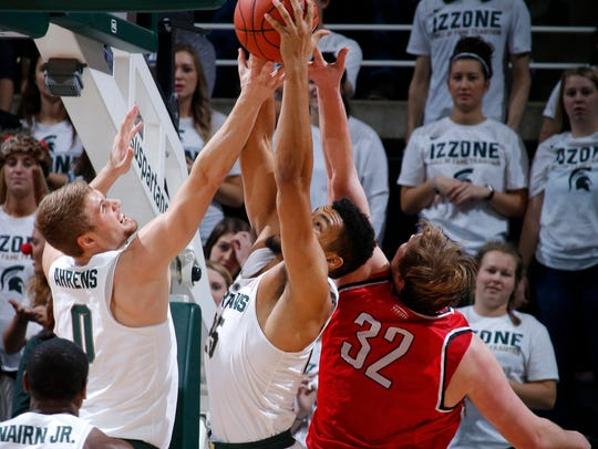 Michigan State's Kyle Ahrens (0) and Kenny Goins, center,
